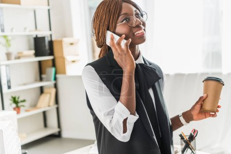 smiling adult african american businesswoman in glasses talking on smartphone and holding coffee to go in office