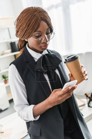 attractive adult african american businesswoman in glasses talking on smartphone and holding coffee to go in office