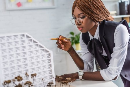 beautiful african american female adult architect in glasses holding pen and working on construction project in office