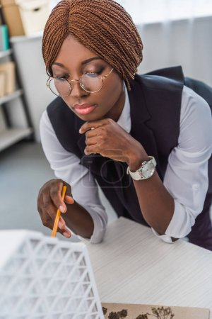 portrait of african american female adult architect in glasses holding pen and working on construction project in office
