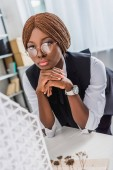 portrait of serious african american adult female architect in glasses and formal wear propping chin with hands while working on construction project in office