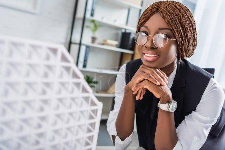 Foto de Arquitecto femenino adultos afroamericano sonriente en gafas y ropa formal, apoyar la barbilla con las manos mientras se trabaja en proyecto de construcción en la oficina - Imagen libre de derechos