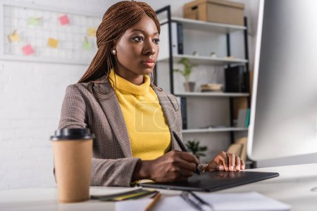 beautiful serious african american adult businesswoman sitting at computer desk and using graphic tablet in office