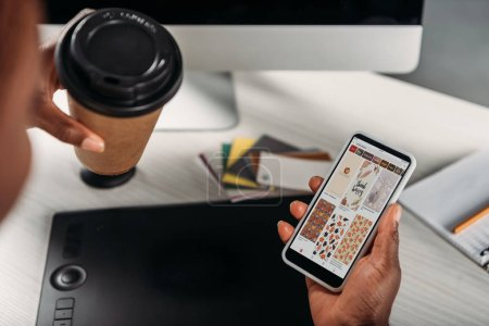 cropped view of african american female adult businesswoman holding coffee to go and smartphone with pinterest app on screen