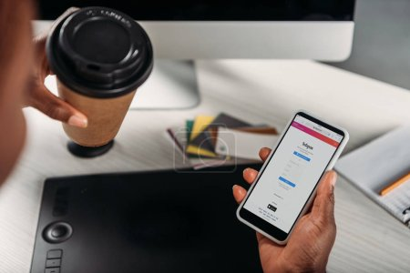 cropped view of african american female businesswoman holding coffee to go and smartphone with instagram app on screen