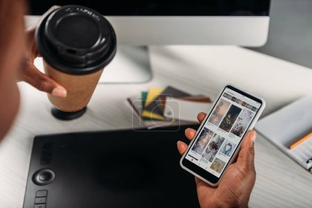 Photo for Cropped view of african american female businesswoman holding coffee to go and smartphone with pinterest app on screen - Royalty Free Image