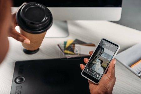 Photo pour Vue recadrée d'une femme d'affaires afro-américaine tenant du café à emporter et d'un smartphone avec une application en ligne à l'écran - image libre de droit