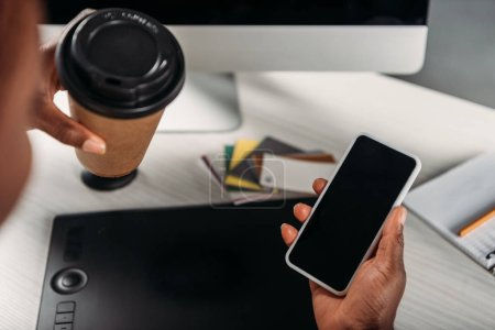 Photo for Cropped view of african american female businesswoman holding coffee to go and smartphone with blank screen - Royalty Free Image