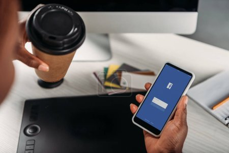 cropped view of african american female businesswoman holding coffee to go and smartphone with facebook app on screen