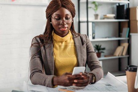 Foto de Hermosa arquitecto mujer afroamericana en glassses con smartphone y trabajando en escritorio con planos en oficina - Imagen libre de derechos