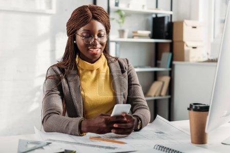 Photo pour Souriant afro-américaine architecte femelle dans des verres à l'aide de smartphone et travaillant au bureau avec les bleus au bureau - image libre de droit