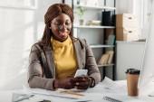 sonriendo el arquitecto mujer afroamericana en vasos con smartphone y trabajando en escritorio con planos en oficina