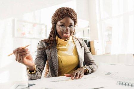 Foto de Sonriendo el arquitecto mujer afroamericana en vasos con lápiz, mirando a cámara y trabajar en proyecto en escritorio con planos en oficina - Imagen libre de derechos