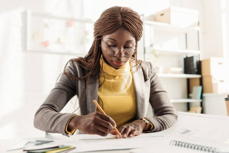 concentrated african american female architect in glasses holding pencil and working on project at desk with blueprints in office