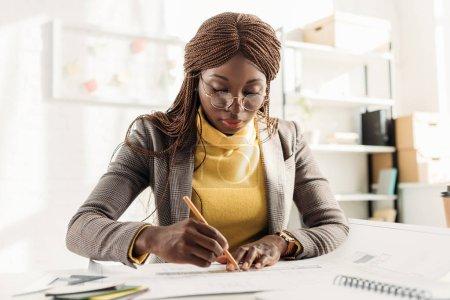 Foto de Concentrado a arquitecto mujer afroamericana en gafas sosteniendo el lápiz y trabajar en proyecto en escritorio con planos en oficina - Imagen libre de derechos