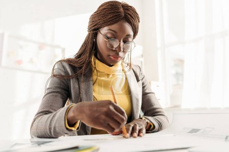 focused african american female architect in glasses holding pencil and working on project at desk with blueprints in office
