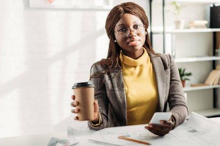 Photo pour Afro-américaine architecte femelle dans les verres, tenant la café d'aller, à l'aide de smartphone et travaillant au bureau de projet avec plans - image libre de droit