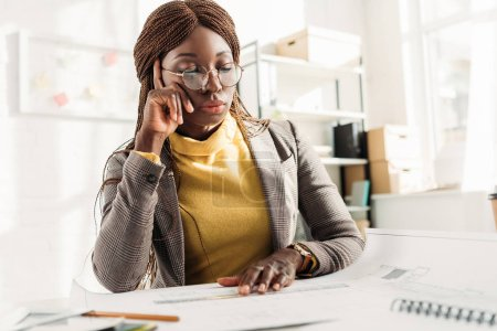 pensive african american female architect in glasses propping head with hand and working on project with blueprints at office desk