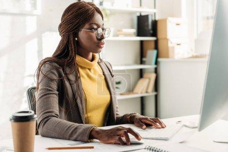 Photo pour Axé sur la femme d'affaires afro-américain assis au bureau de l'ordinateur et au bureau - image libre de droit