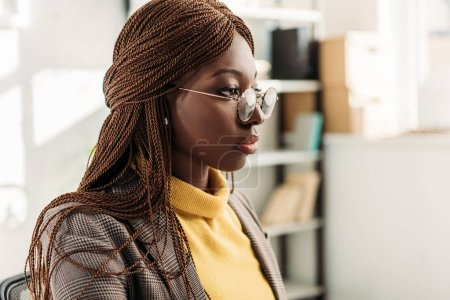 portrait of stylish african american adult businesswoman in formar wear and round glasses