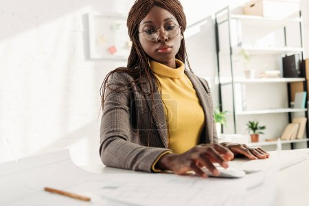 concentrated african american female architect in glasses and formal wear working on project with blueprints at office desk