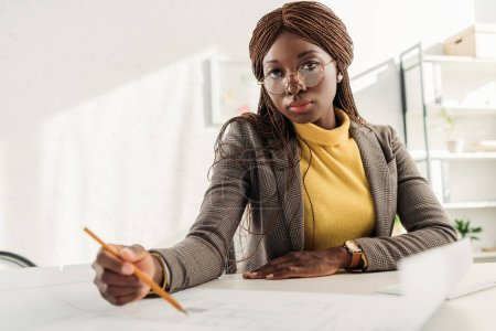 Photo for Serious african american female architect in glasses holding pen and working on project at desk with blueprints in office - Royalty Free Image