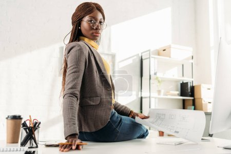Photo pour Confiant architecte femelle afro-américaine dans des verres en regardant la caméra et la tenue de plan directeur au bureau - image libre de droit