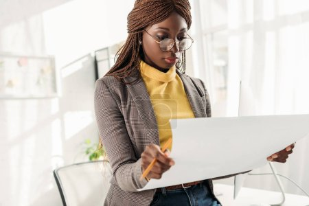 focused african american female architect in glasses holding blueprint and pencil in office