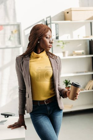 beautiful african american adult businesswoman in formal wear and glasses holding coffee to go and posing at modern office