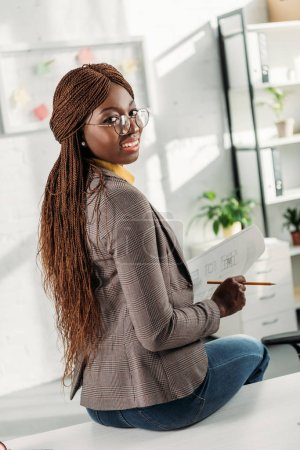 Photo for Smiling african american female architect in glasses sitting on office desk, looking at camera and holding blueprint with pencil - Royalty Free Image