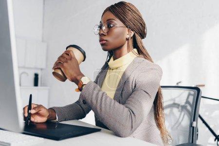 grave afro-américaine adulte femme d'affaires assis au bureau de l'ordinateur, boire du café et en utilisant une tablette graphique