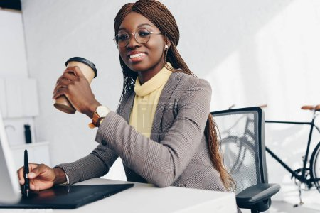 beautiful smiling african american businesswoman using graphics tablet, drinking coffee to go and looking at camera at workplace