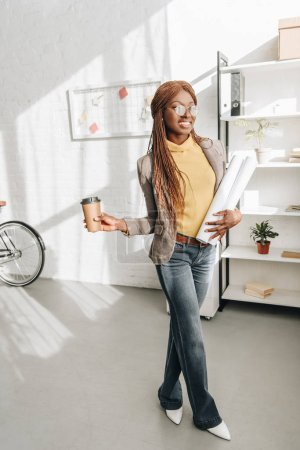 happy african american adult female architect in glasses holding coffee to go and blueprints at workplace