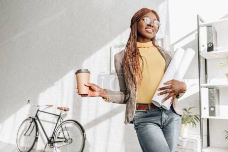 smiling african american adult female architect in glasses holding coffee to go and blueprints at workplace