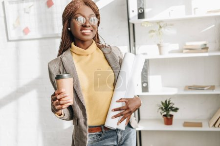 cheerful african american adult female architect in glasses holding coffee to go and blueprints at workplace