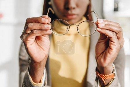 Photo pour Vue recadrée de femme d'affaires adulte afro-américaine en tenue de cérémonie portant des lunettes - image libre de droit