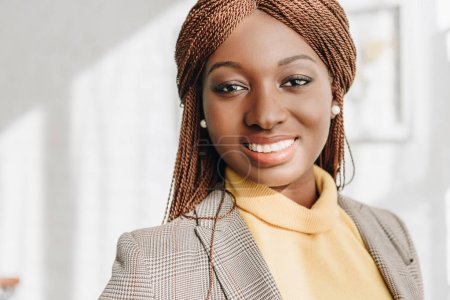 portrait of stylish smiling african american adult businesswoman looking at camera