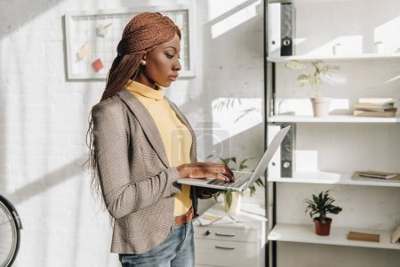 side view of serious african american adult businesswoman holding laptop at workplace