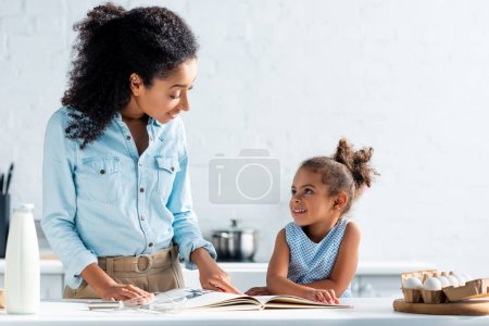 cheerful african american mother and daughter looking at each other, cookbook on table in kitchen