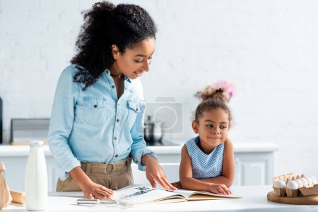 african american mother and daughter reading recipe book in kitchen