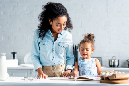 smiling african american mother and daughter looking at cookbook together in kitchen