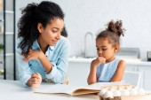 pensive african american mother and daughter choosing recipe from cookbook in kitchen