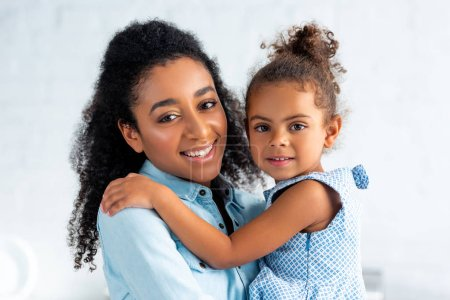 smiling african american mother and daughter hugging in kitchen and looking at camera
