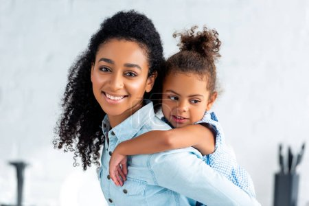 smiling african american mother giving piggyback to daughter in kitchen and looking at camera