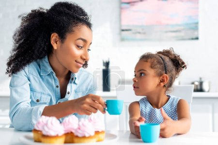african american mother and daughter with tiaras holding plastic cups and looking at each other in kitchen