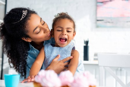 african american mother hugging excited daughter at table with cupcakes in kitchen