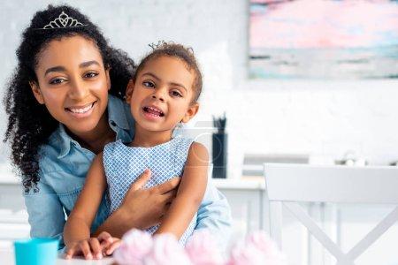 sonrisa de madre afroamericana hija abrazando a la mesa con cupcakes en cocina