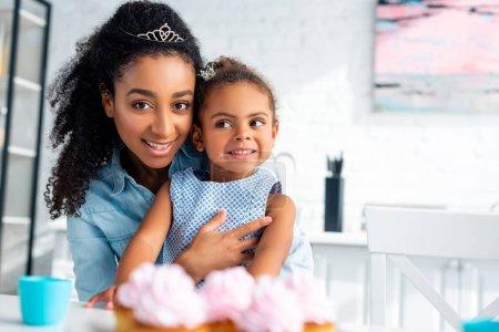 madre afroamericana atractivo hija abrazando a la mesa con cupcakes en cocina