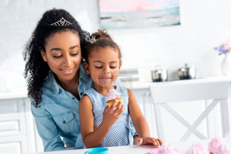 african american mother and daughter looking at cupcake in kitchen