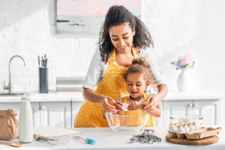Photo for Smiling african american mother helping daughter breaking egg for preparing dough in kitchen - Royalty Free Image
